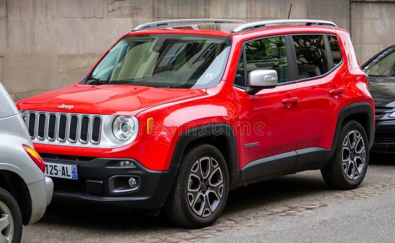 Nya röda Jeep Renegade som parkeras mellan till bilar royaltyfri fotografi