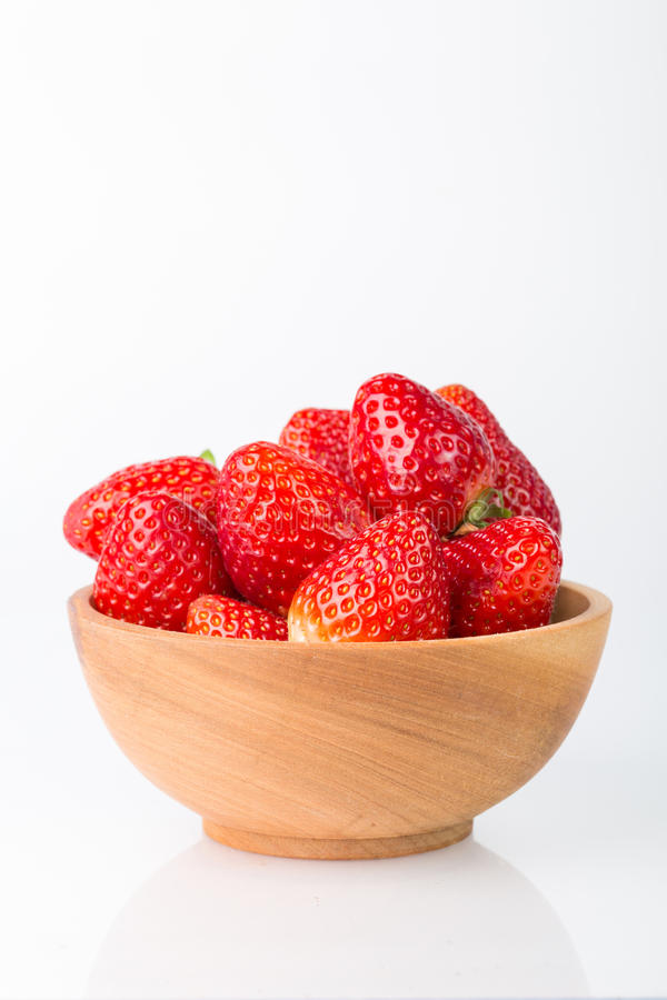Nya röda jordgubbar i en träbunke royaltyfri foto