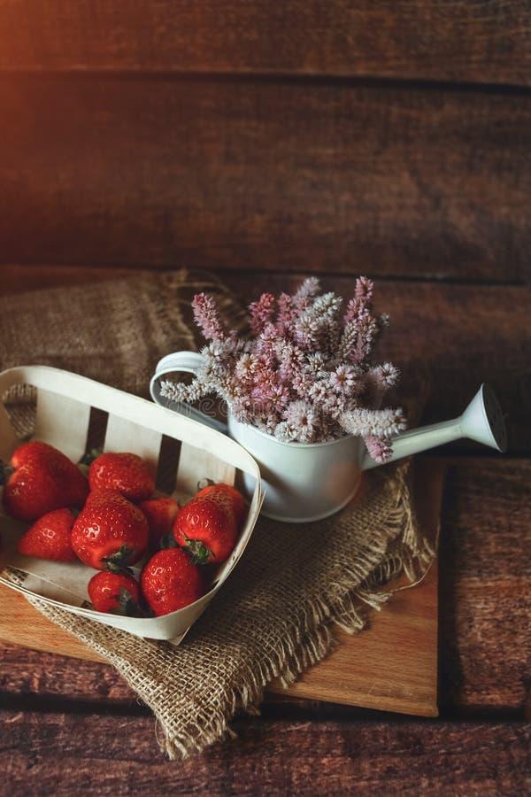 Nya röda jordgubbar på trätabellen med sommarblommor, frukost som tonas royaltyfria foton