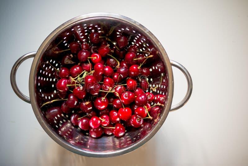 Nya röda körsbär som är influten durkslag organiska röda söta körsbär i ståldurkslag på vit bakgrund Sunt royaltyfria foton