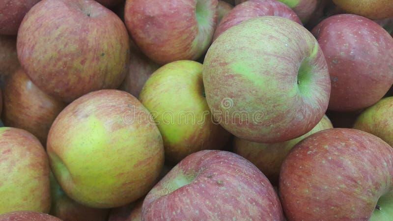 Nya röda och gröna äpplen traver i den till salu marknaden arkivfoton