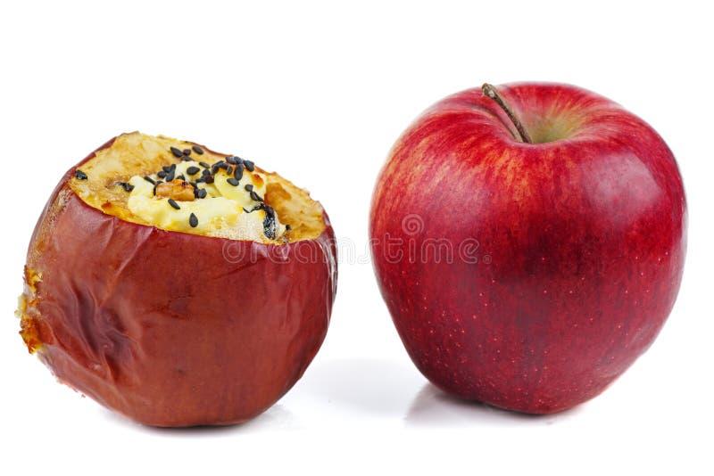 Nya röda och välfyllda bakade äpplen med sezamefrö och valnötter som isoleras på en vit bakgrund arkivfoton