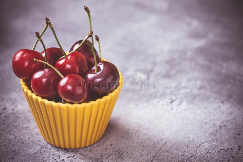 Nya röda organiska körsbär i gul bunke som sommarbegrepp fotografering för bildbyråer