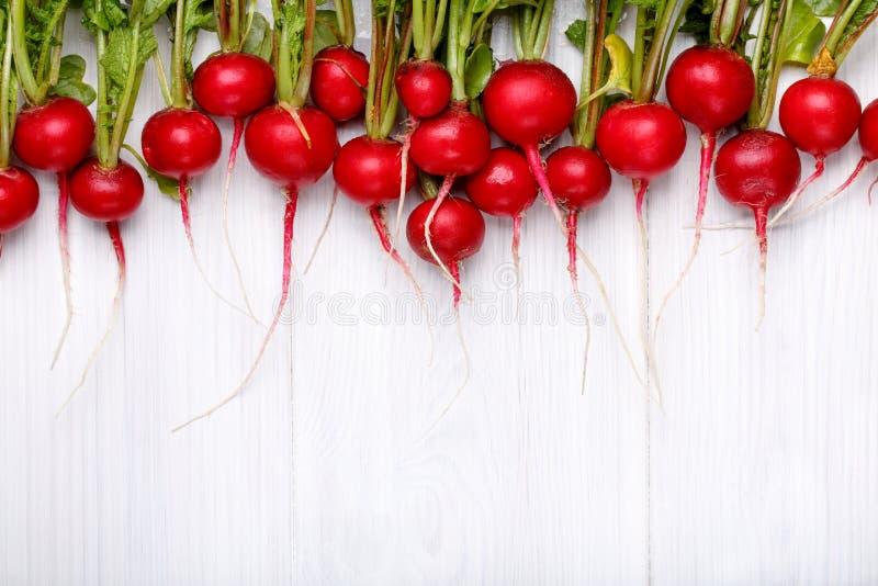 Nya röda rädisor med blast i linje på den vita trätabellen arkivbilder