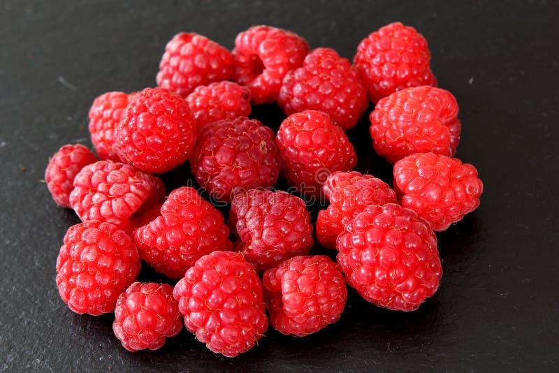 Nya röda raspberriy frukter på en kritiseraplatta royaltyfri foto