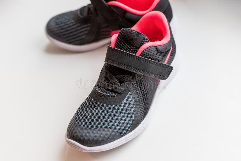 Nya rosa färger, svarta sportskor på vit bakgrund lurar rinnande skor Rinnande skor för barn` s På a arkivbild