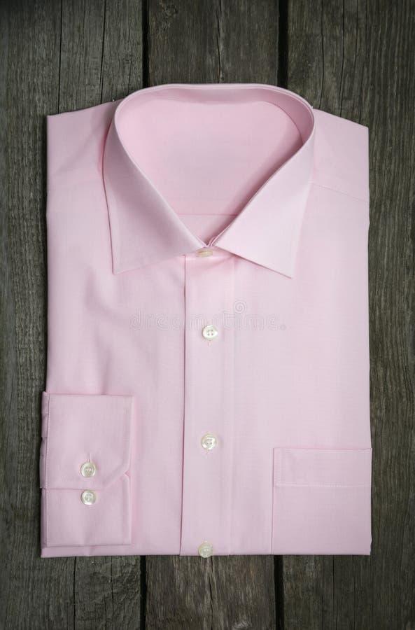 Nya rosa mäns skjorta på träbakgrund royaltyfri fotografi