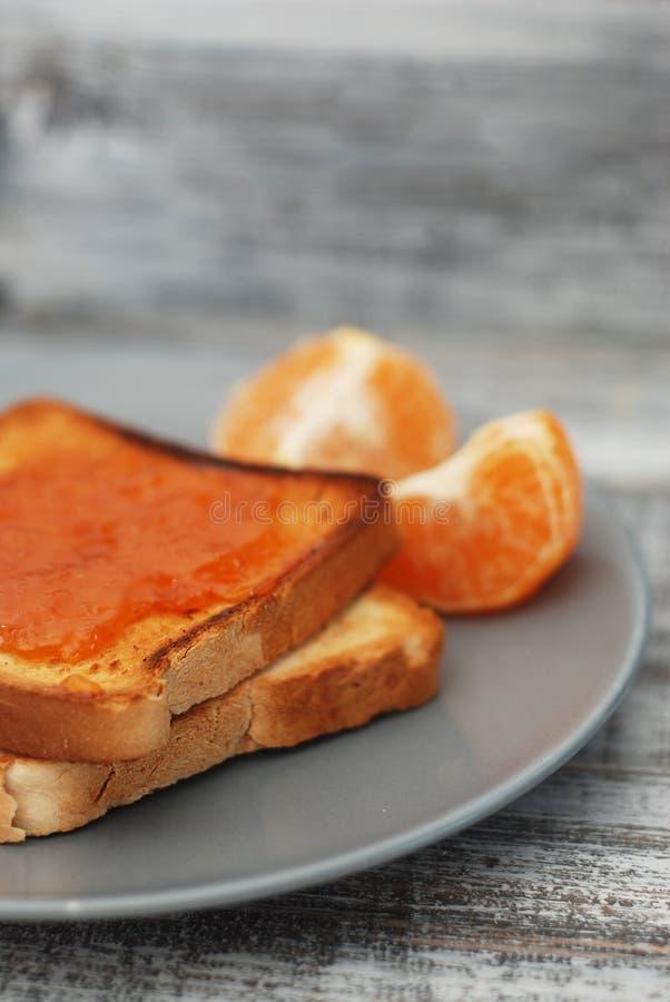 Nya rostade bröd med hemlagat orange driftstopp på Gray Plate över träbakgrund arkivfoto