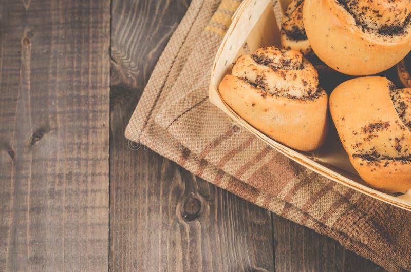 Nya rullar med vallmo en träask/ett nytt bakelsebegrepp: nya rullar med vallmo en ask på en mörk träbakgrund, en bästa sikt och fotografering för bildbyråer