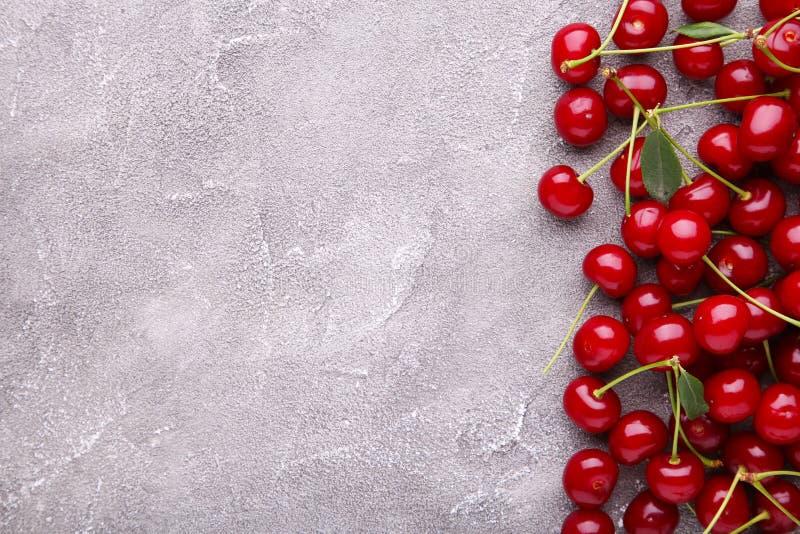 Nya söta körsbär med sidor på grå konkret bakgrund, bästa sikt royaltyfri foto