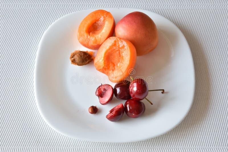 Nya söta röda körsbär med orange aprikors på en vit platta royaltyfri bild