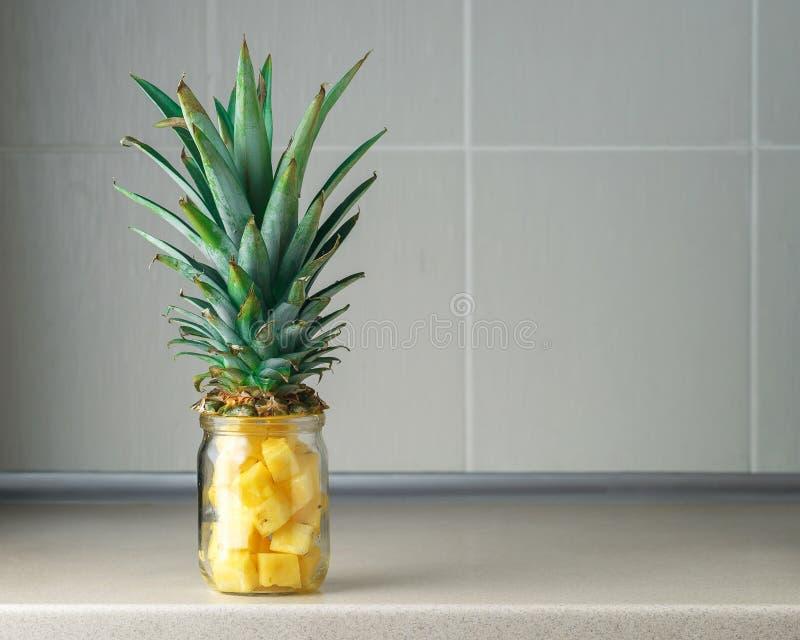 Nya saftiga ananasstycken i en glass krus royaltyfri bild