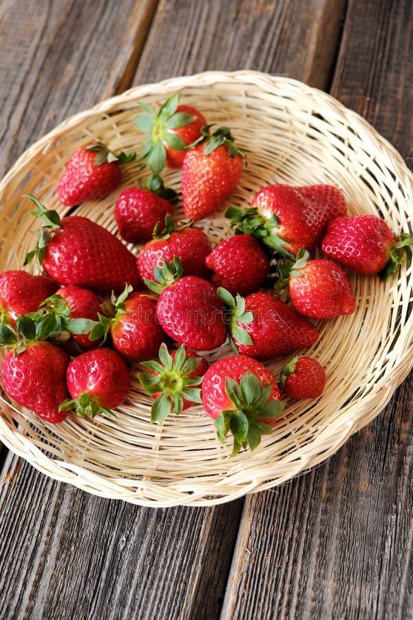Nya saftiga jordgubbar i en träkorg på tabellen royaltyfri bild
