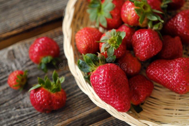 Nya saftiga jordgubbar i en träkorg på tabellen arkivfoton