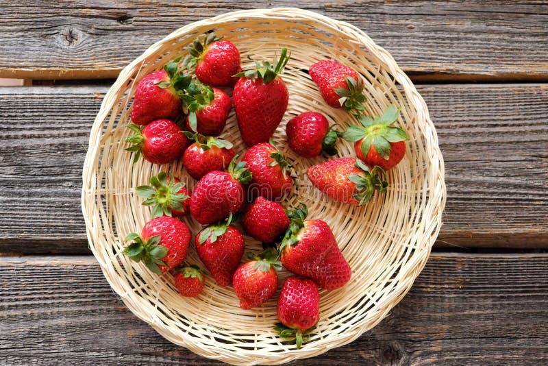 Nya saftiga jordgubbar i en träkorg på tabellen arkivfoto