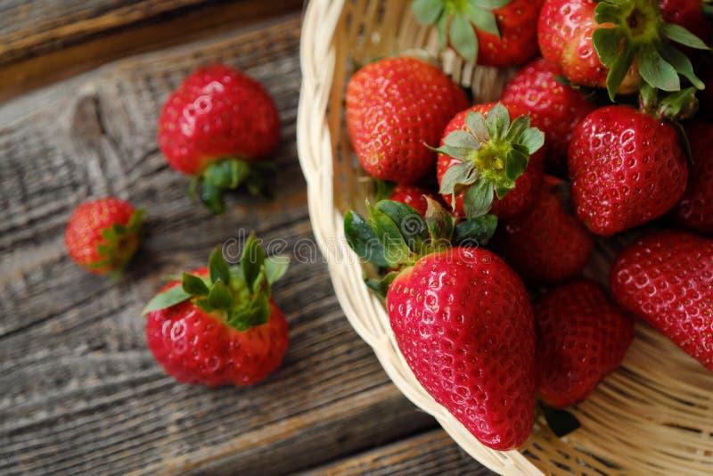 Nya saftiga jordgubbar i en träkorg på tabellen arkivbild