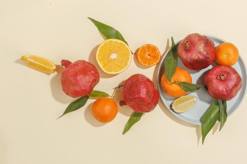 Nya saftiga tangerin, granatäpplen och skivade frukter på en gul bakgrund Sommarlynne, sund mat Top beskådar royaltyfri bild
