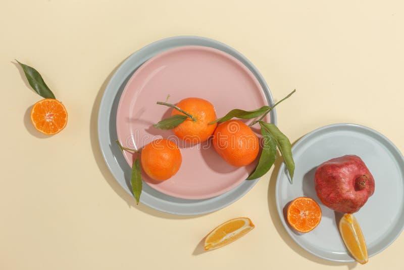 Nya saftiga tangerin, granatäpplen och skivade frukter på en gul bakgrund Sommarlynne, sund mat Top beskådar arkivbilder