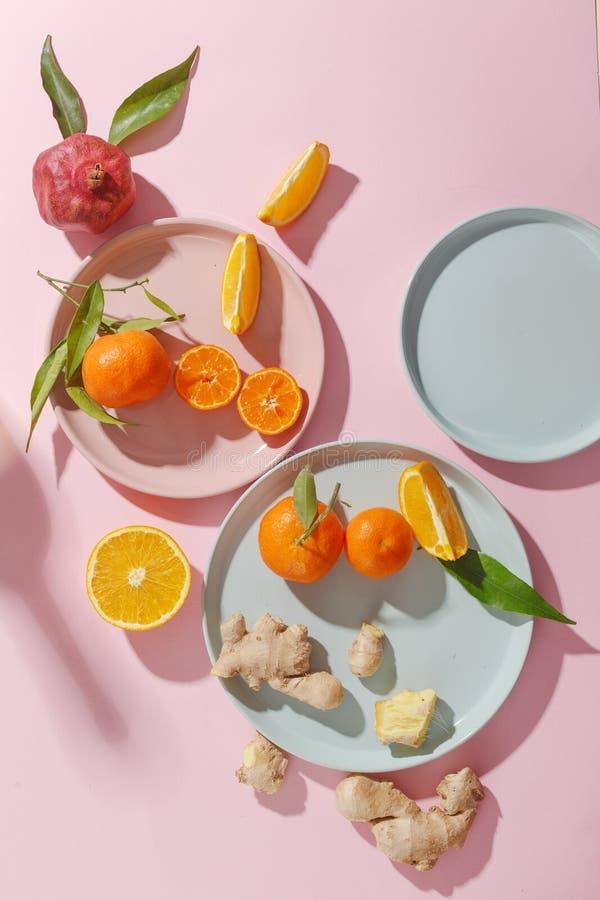 Nya saftiga tangerin, granatäpplen och skivade frukter på kulöra plattor på en rosa bakgrund Sommarlynne, sund mat Top beskådar royaltyfria foton