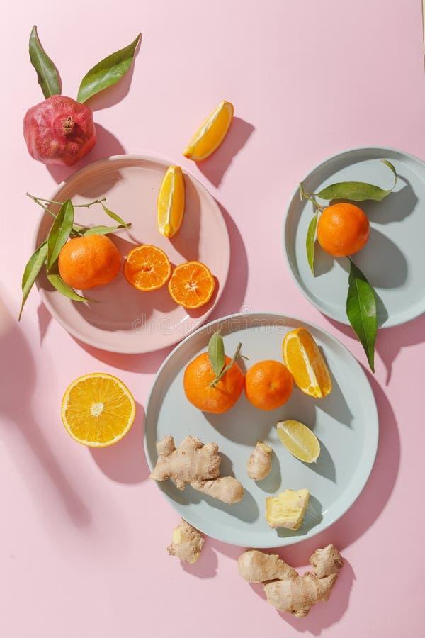 Nya saftiga tangerin, granatäpplen och skivade frukter på kulöra plattor på en rosa bakgrund Sommarlynne, sund mat Top beskådar royaltyfri fotografi