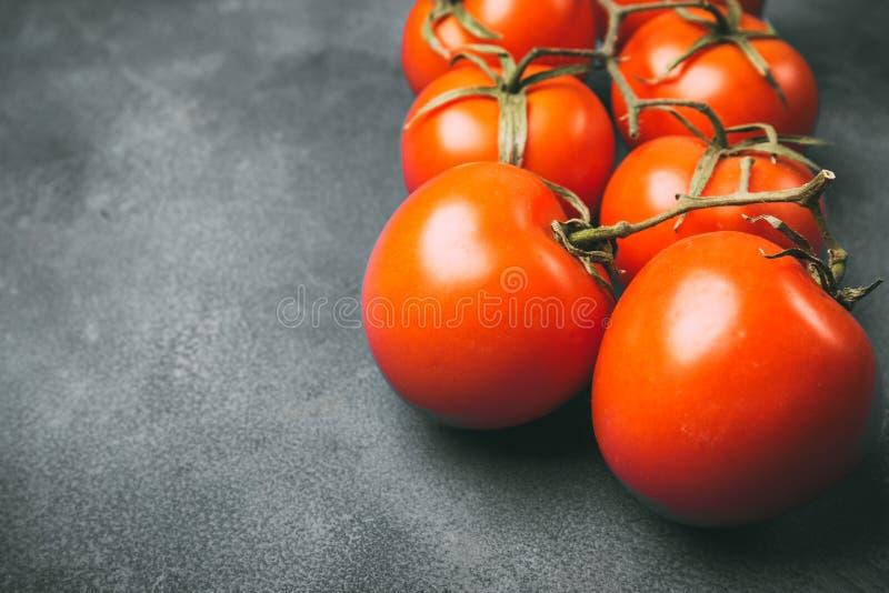 Nya saftiga tomater på en grå bakgrund royaltyfri foto