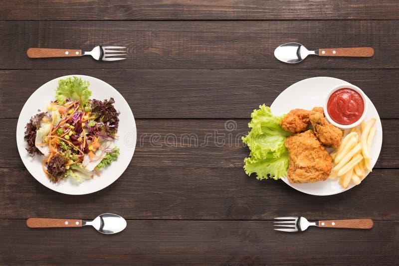Nya sallad och stekt kyckling- och fransmansmåfiskar på träbacen royaltyfri bild