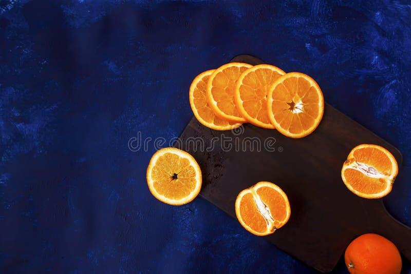 Nya skivade apelsiner på träbräde fotografering för bildbyråer