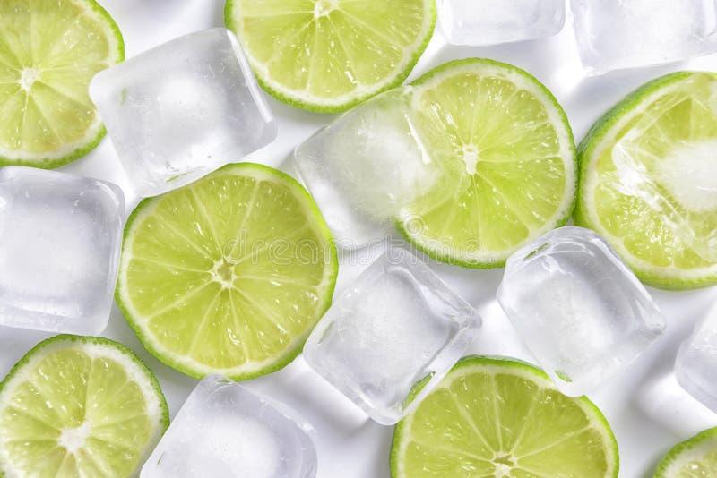 Nya skivade mogna limefrukt- och iskuber p? vit bakgrund arkivbilder