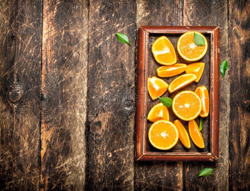 Nya skivor av apelsiner i det gamla magasinet arkivbilder