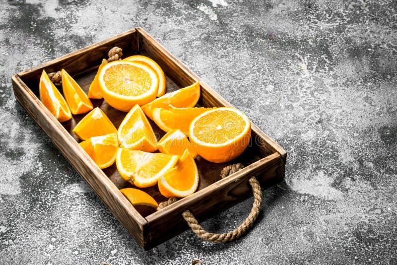 Nya skivor av apelsiner i ett trämagasin royaltyfri foto