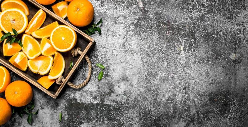 Nya skivor av apelsiner i ett trämagasin fotografering för bildbyråer