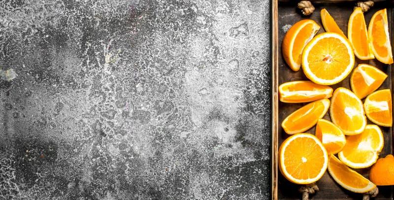 Nya skivor av apelsiner i ett trämagasin arkivbilder