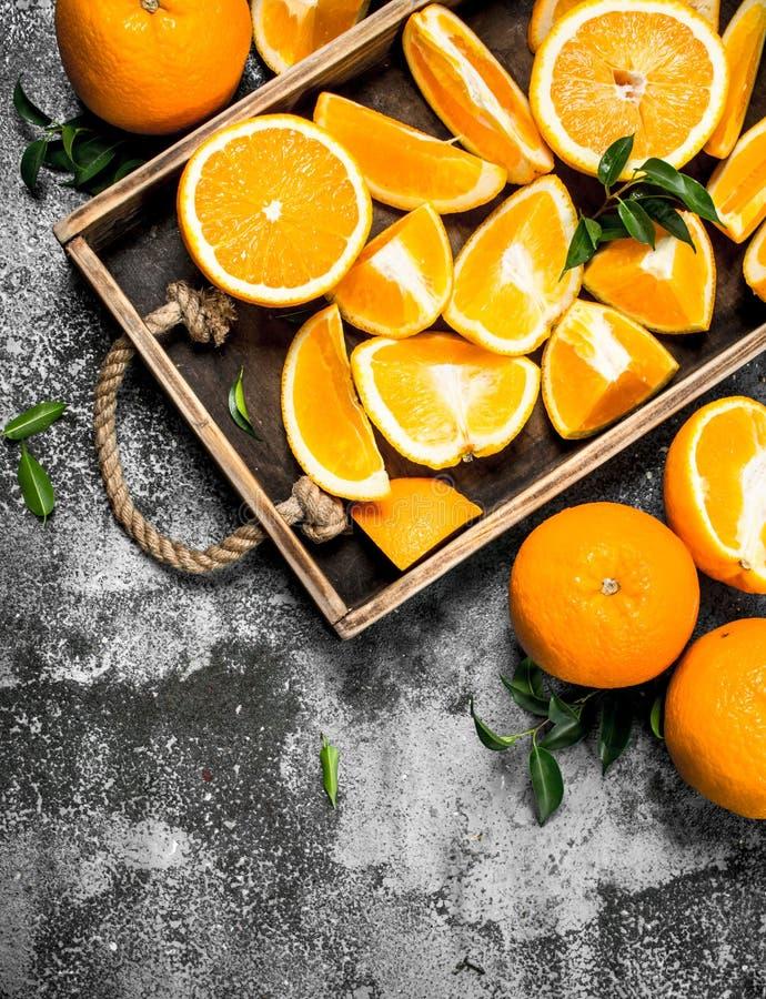 Nya skivor av apelsiner i ett trämagasin arkivfoto