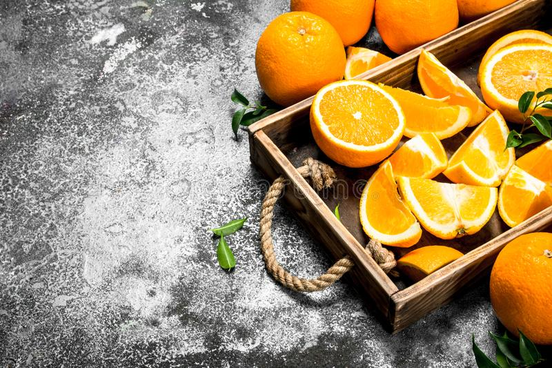 Nya skivor av apelsiner i ett trämagasin royaltyfri fotografi