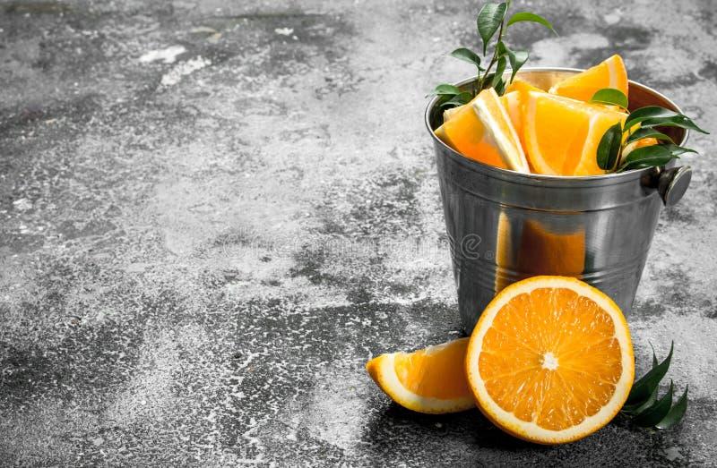 Nya skivor av apelsiner i stålhink fotografering för bildbyråer