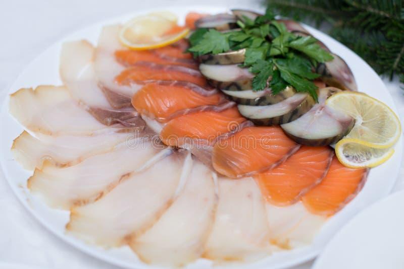 Nya skivor av laxen, den röda fisken och sillen på en vit platta i en restaurang Fiskuppläggningsfatet dekoreras med skivor av ny arkivbild
