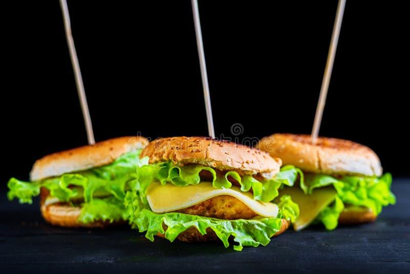 Nya smakliga tre hamburgare på svart bakgrund royaltyfri bild