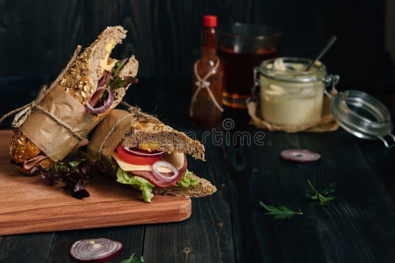 Nya smakliga ubåtsmörgås och såser på den trämörka fliken arkivfoton