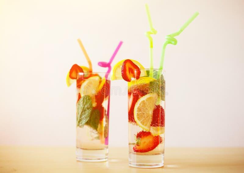 Nya sommardrinkar med citronen, jordgubben och mintkaramellen på trätabellen arkivfoto