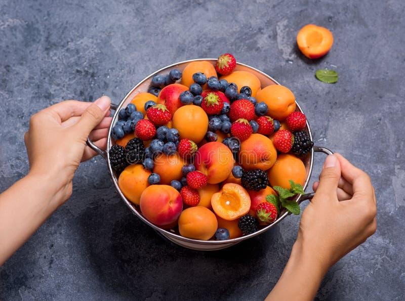 Nya sommarfrukter och bär, aprikors, blåbär, jordgubbar i durkslag, kvinnas händer som rymmer durkslaget med frukter och royaltyfria bilder