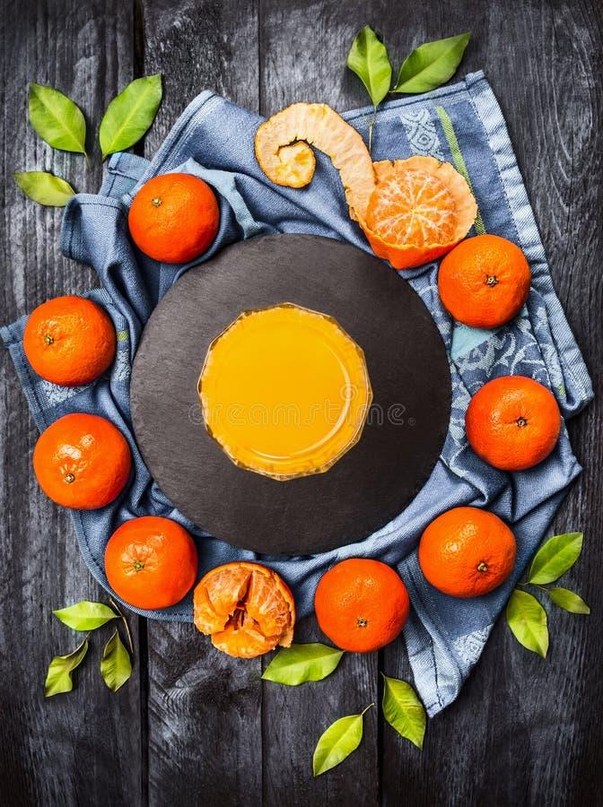 Nya tangerin med sidor och exponeringsglas av citrus fruktsaft på blå träbakgrund arkivbilder