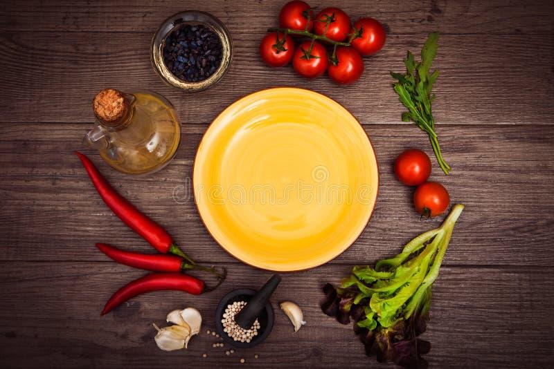 Nya tomater, chilipeppar och andra kryddor och örter runt om den moderna gula plattan i mitten av trätabellen Top beskådar Kopia  arkivbild