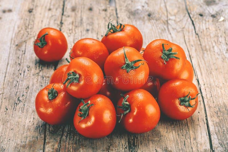 Nya tomater på en gammal trätabell Växa av frukter och grönsaker sund mat Rå vegetarisk mat Sale av tomater arkivfoton