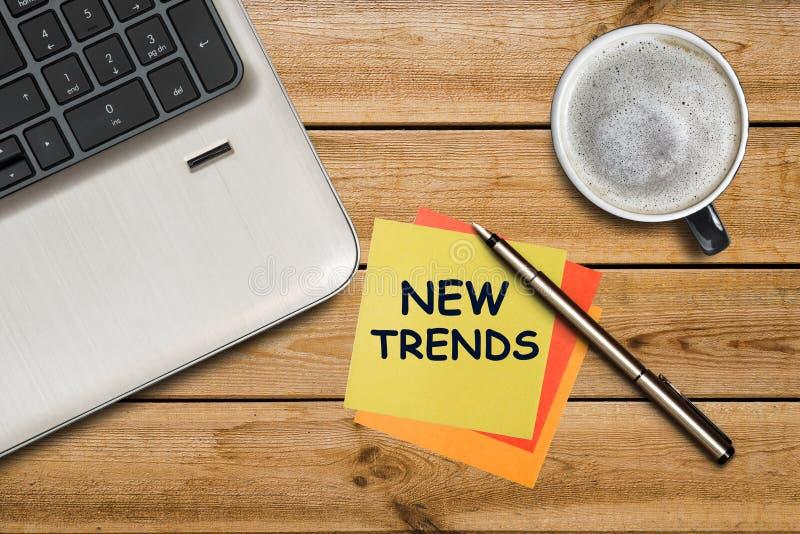 Nya trender som är skriftliga på en gul klistermärke som ligger på en trätabell Nya trender av affärsidéen för nytt år arkivfoton