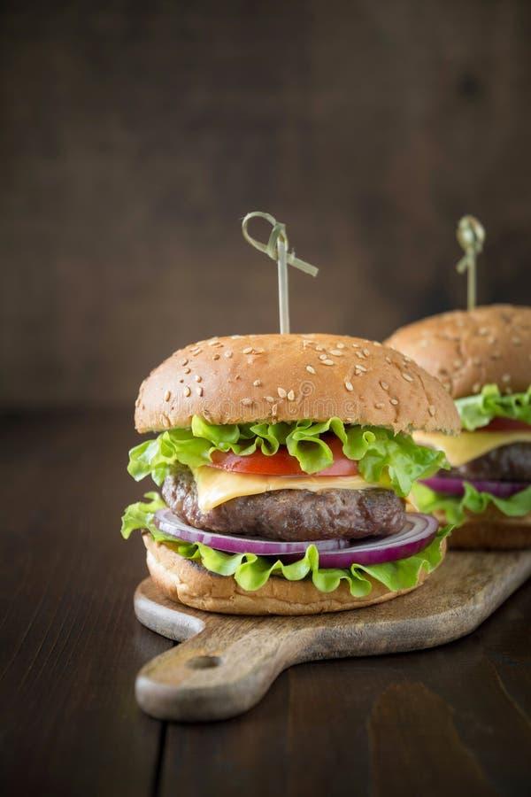 Nya två nötkötthamburgare med grönsaker på träbräde deltagare Bl?ttskyen, stillhet bevattnar fotografering för bildbyråer