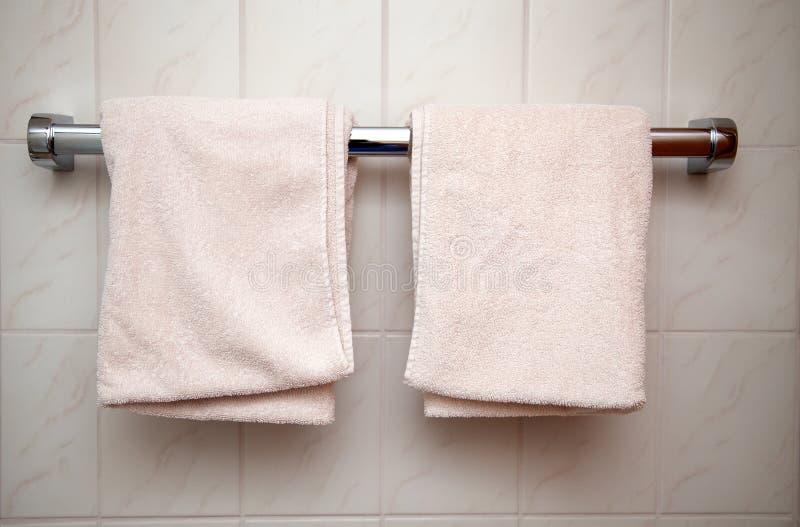 Nya två och rena handdukar som hänger i ett badrum royaltyfri bild