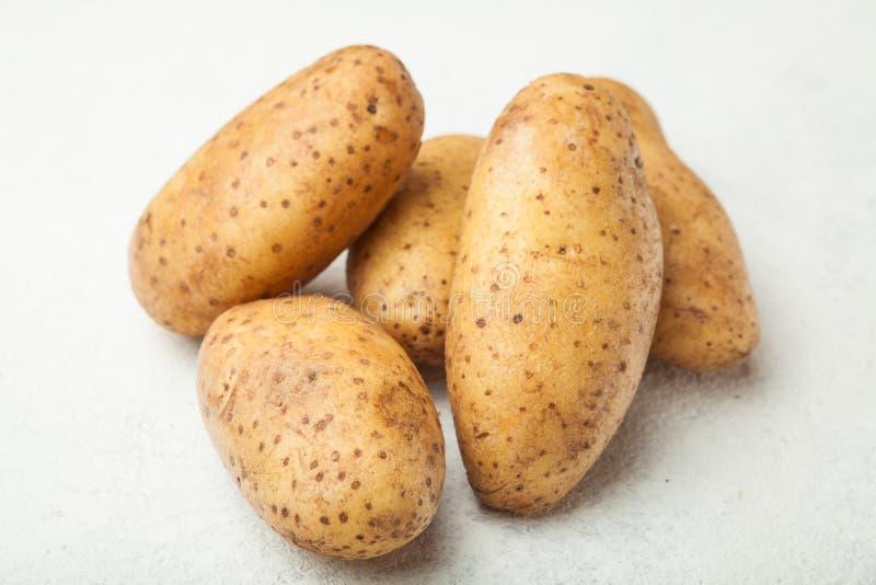 Nya unga potatisar på en vit tabell royaltyfri foto
