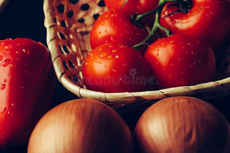 Nya våta tomater i droppar av vatten, guld- lök, spansk peppar på mörk bakgrund arkivbild