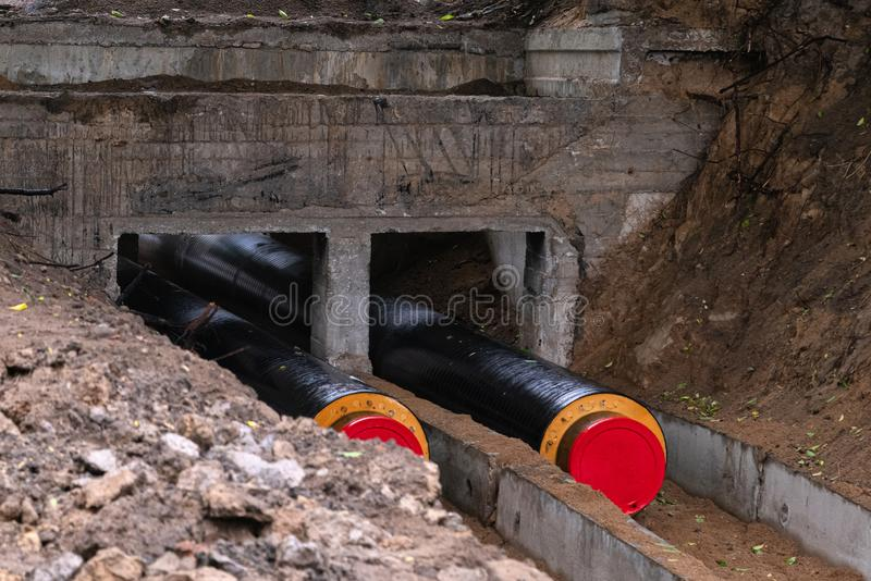 Nya vattenrör som ner djupt läggas in i jordningen Konstruktionsplats, huvudsaklig vattenlinje i diket arkivfoton