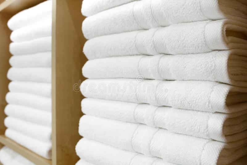 Nya vita hotellhanddukar vikta och som staplas på en hylla royaltyfria bilder